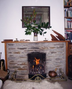 A fragrant, cozy fire in the stone fireplace at Landfall Cottage